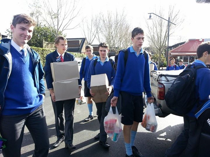 Rosmini College students load up the van with the proceeds of their can drive