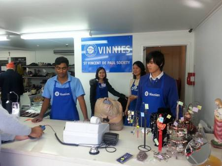 Rosmini College Students merchandising, restocking and sorting goods for sale